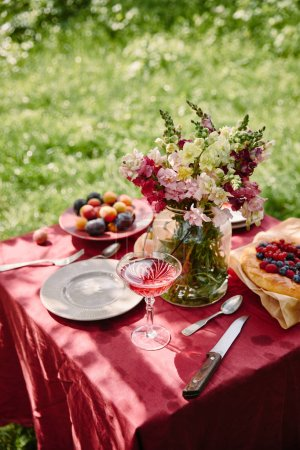wineglass and bouquet of flowers on table in garden