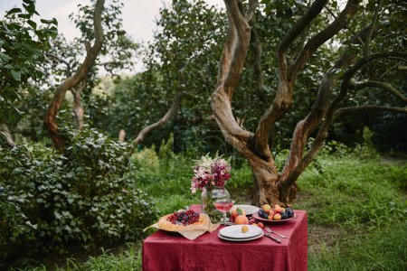 berries pie and bouquet of flowers on table in garden with trees