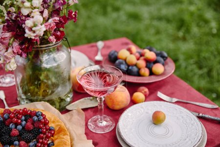 Photo for Berries pie, wineglass and bouquet of flowers on table in garden - Royalty Free Image