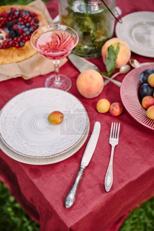 Photo for Plates, fork and knife on table in garden - Royalty Free Image