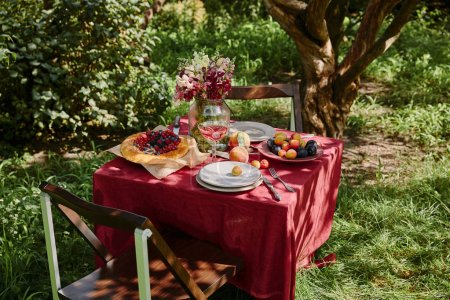 bouquet of flowers, fruits and pie on table in garden