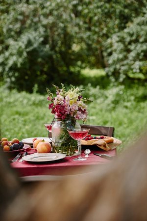 bouquet of flowers and fruits on table in garden