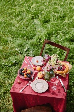 Photo pour Vue de la forte inclinaison de table avec fruits, tarte et fleurs de jardin - image libre de droit