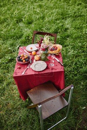 Photo pour Vue d'angle élevé de table avec fruits, tarte et assiettes dans le jardin - image libre de droit