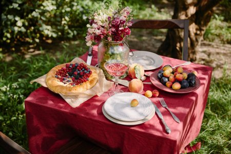 wineglass, berries pie and fruits on table in garden