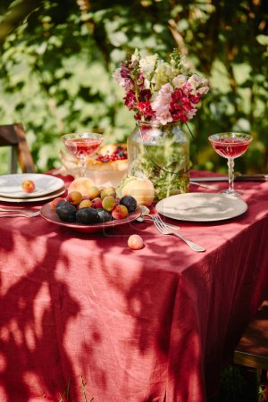 yummy fruits, wineglasses and bouquet of flowers on table in garden