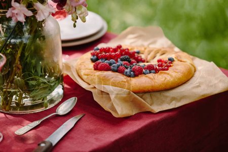 Photo for Appetizing pie with raspberries, currants and blueberries on table in garden - Royalty Free Image