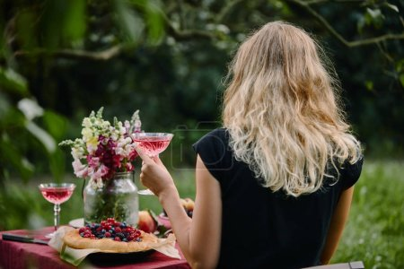 rear view of woman holding glass of wine at table in garden