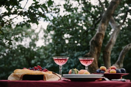 glasses of wine, berries pie and fruits on table for dinner in garden
