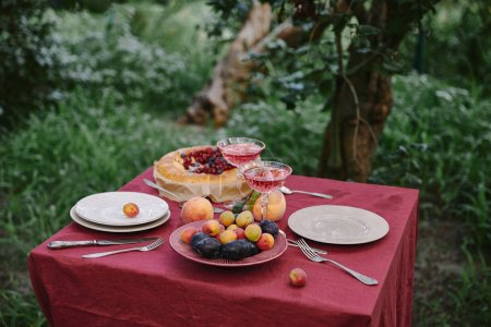 glasses of wine, berries pie, plates and fruits on table in garden