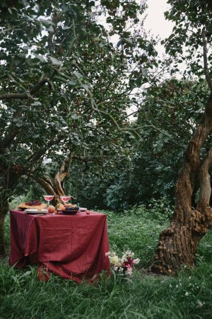 served table with red tablecloth in garden