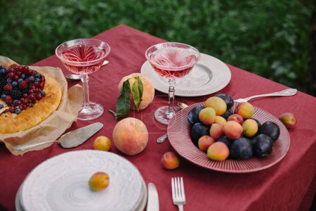 glasses of wine, berries pie and fruits on table in garden