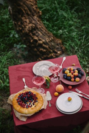Photo for Cooked berries pie and glasses of wine on table in garden - Royalty Free Image