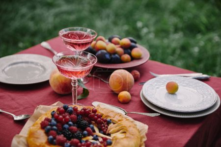 delicious berries pie and glasses of wine on table in garden
