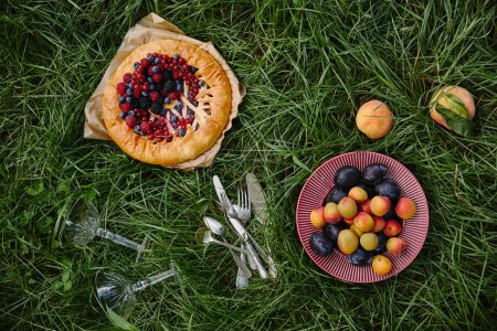 elevated view of pie with berries, plate with fruits and utensils on green grass