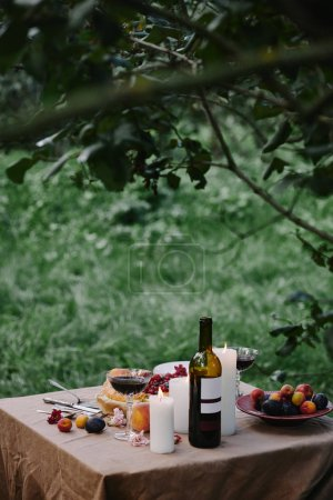 candles, wine bottle and fruits on table in garden for dinner