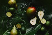 top view of fresh ripe fruits, ice cubes and beautiful green tropical leaves