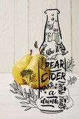 two yellow organic pears on wooden background with illustration of cider bottle and flowers