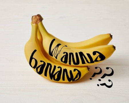 "raw fresh yellow bananas on wooden background with ""Wanna banana?"" question"