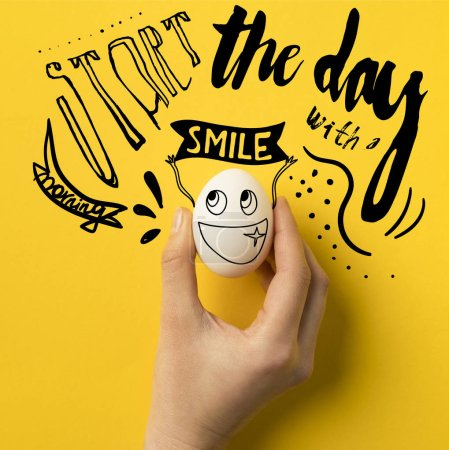 "cropped image of woman holding egg isolated on yellow with ""Start the day with a smile"" inspiration"