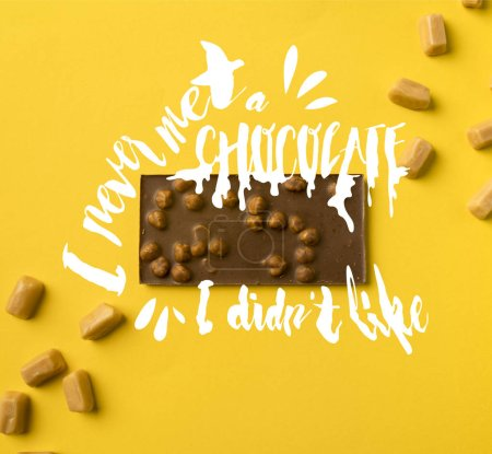 "Top view of chocolate bar with scattered iris milk candies isolated on yellow with ""I never met a chocolate, I didnt like"" lettering"