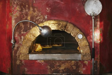 Photo for Close-up shot of masonry oven at restaurant kitchen with baking pizza inside - Royalty Free Image