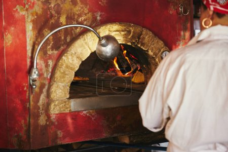 Photo for Cropped shot of chef taking pizza from brick oven at restaurant kitchen - Royalty Free Image
