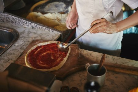 cropped shot of chef pouring ketchup onto pizza dough at restaurant kitchen