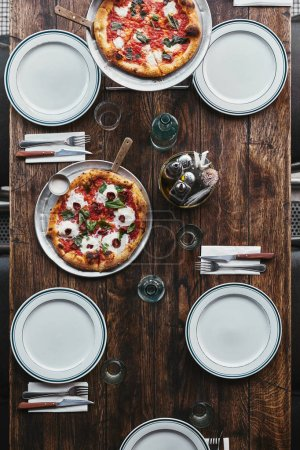 top view of delicious pizza margherita on tray and plates on rustic table at restaurant