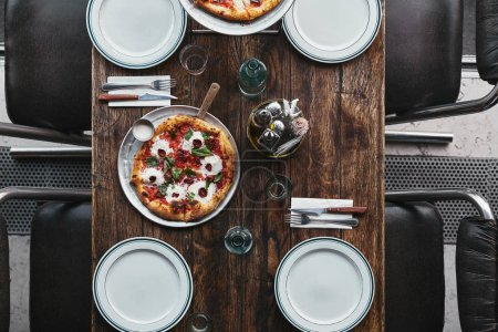 Photo for Top view of tasty pizza margherita on tray and plates on rustic table at restaurant - Royalty Free Image