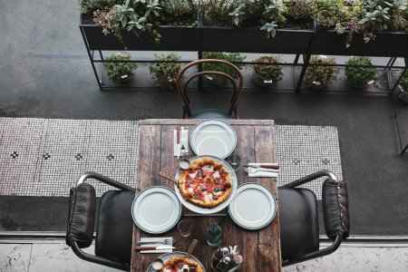 Photo for Top view of tasty pizza margherita on tray and table setting at restaurant - Royalty Free Image