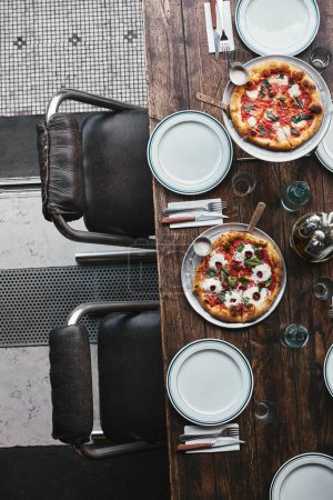 Photo for Top view of various delicious pizza on trays at restaurant - Royalty Free Image