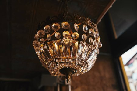 close-up shot of vintage chandelier hanging from ceiling of restaurant