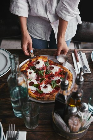 cropped shot of serving delicious pizza on restaurant table with water