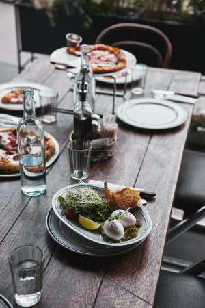 Photo for Delicious salad and pizza on table at modern restaurant - Royalty Free Image