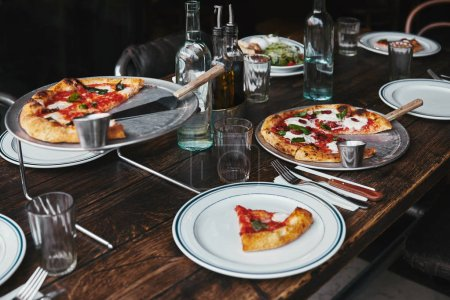 delicious pizza and water on table at modern restaurant