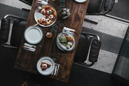 top view of delicious pizza and salad on wooden table at restaurant