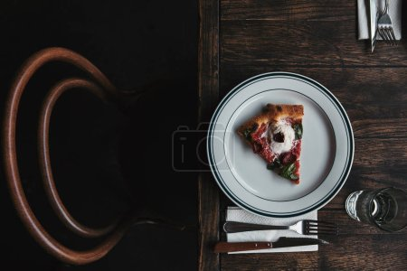 top view of delicious pizza slice on plate with setting and on rustic wooden table