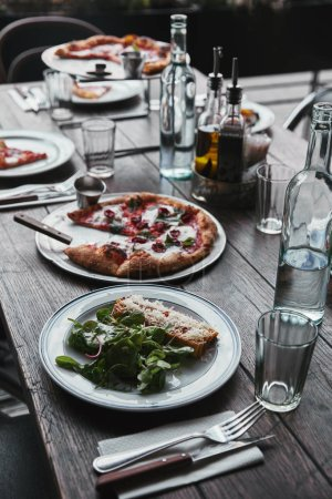 tasty italian dishes and drinks on wooden rustic table at restaurant