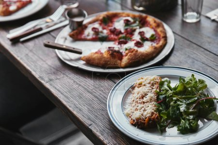close-up shot of tasty pizza and lasagne on wooden table