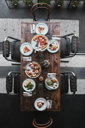 top view of different italian dishes and drinks on wooden rustic table at restaurant