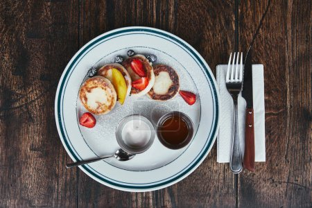 top view of cheese pancakes with bowls of dippings and cutlery on rustic wooden table