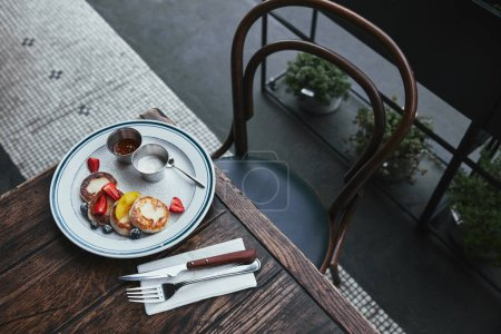 Photo for Tasty curd pancakes with bowls of dippings and cutlery on wooden table at restaurant - Royalty Free Image