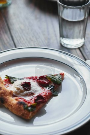 close-up shot of tasty pizza margherita on white plate with glass of water