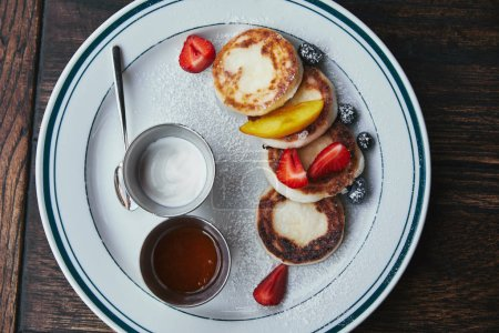 top view of delicious cheese pancakes with bowls of dippings on wooden table