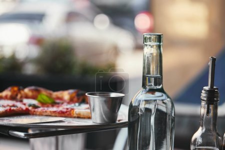 close-up shot of delicious pizza on tray and bottle of water at restaurant