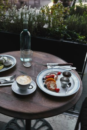 syrniki with coffee and salad on wooden table at restaurant
