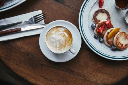 top view of cup of coffee and syrniki with berries on wooden table