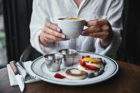 cropped shot of woman holding cup of coffee at restaurant above cheese pancakes on table