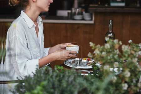 cropped shot of young woman holding cup of coffee at restaurant